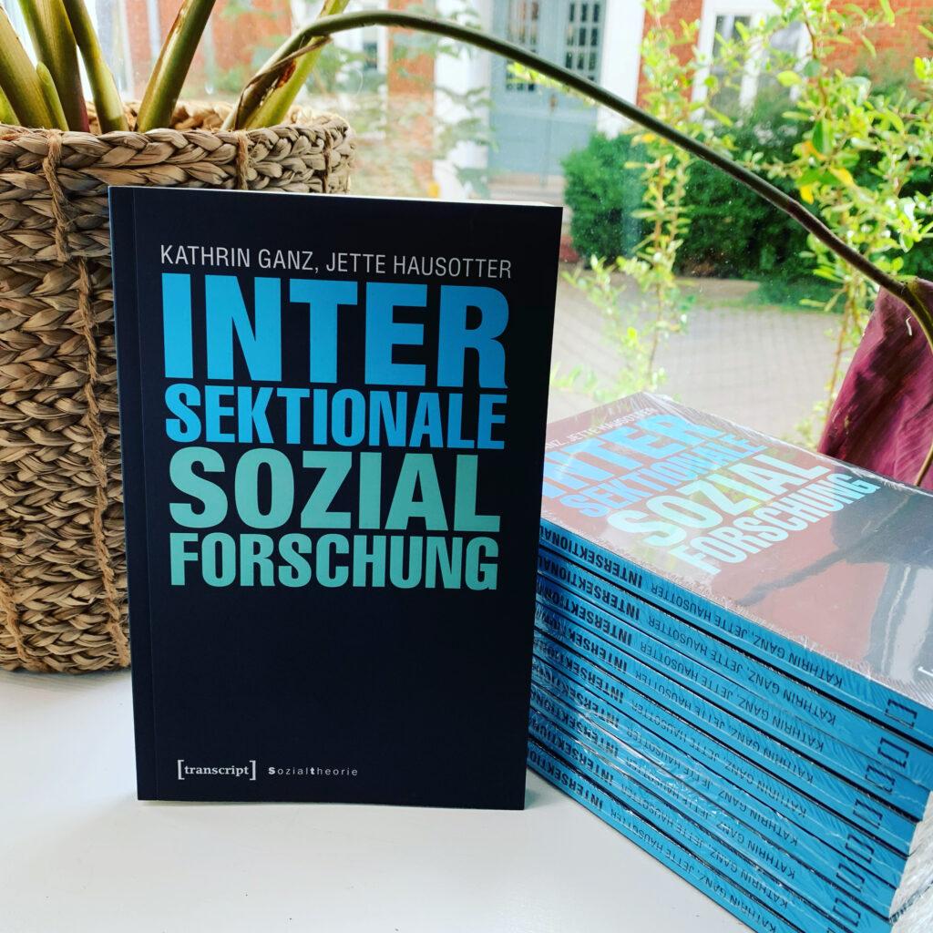 """Buch """"Intersektionale Sozialforschung"""" neben einem Stapel weiterer Ausgaben des Buches auf einer Fensterbank."""